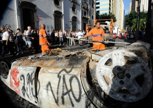 Municipal employees work to remove a burned car during a protest, in Rio de Janeiro, Brazil, Tuesday, June 18, 2013.  (Agencia Brasil / Tania Rego)