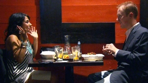A woman holds up her hands during a conversation as she speaks to a man while eating at a restaurant.