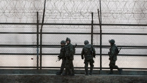 South Korean army soldiers patrol along a barbed-wire fence near the demilitarized zone between the two Koreas in Paju, South Korea, Monday, March 2, 2015. (AP Photo/Ahn Young-joon)