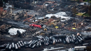 In this file photo, workers comb through debris after a train derailed causing explosions of railway cars carrying crude oil in Lac-Megantic, Que., Tuesday, July 9, 2013. (Paul Chiasson / THE CANADIAN PRESS)