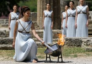 A dancer dressed as priestesses lights the Olympic flame with a parabolic mirror during the ceremonial lighting of the Olympic flame in Ancient Olympia, Greece, Thursday, April 21, 2016. (AP / Thanassis Stavrakis)