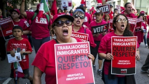 "Hundreds of May Day marchers chanting slogans and carrying signs - these say 'Immigrant Workers Want Respect""- and at least one Donald Trump pinata, take to the streets of Los Angeles, calling for immigrant and worker rights and decrying what they see as hateful presidential campaign rhetoric, Sunday, May 1, 2016. (David Crane / Los Angeles Daily News)"