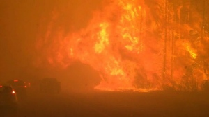 Fire burns near a road in Fort McMurray, Alta., on Tuesday May 3, 2016.  (THE CANADIAN PRESS/Holly Ayearst)