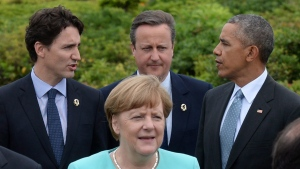 Canadian Prime Minister Justin Trudeau, left, talks with British Prime Minister David Cameron, middle back, and U.S. President Barack Obama as they walk behind German Chancellor Angela Merkel while on their way to an official family photo in Shima, Japan during the G7 Summit on Thursday, May 26, 2016. (THE CANADIAN PRESS/Sean Kilpatrick)