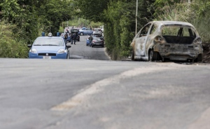 The burned car belonging to slain 22-year-old student Sara Di Pietrantonio is seen along a street in the outskirts of Rome, Monday, May 30, 2016. (Massimo Percossi/ANSA via AP)