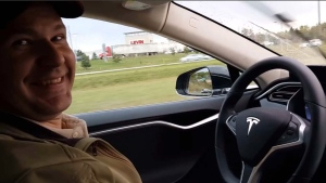 This still image taken from a video published on YouTube on Oct. 15, 2015, shows Joshua Brown of Canton, Ohio, in the driver's seat of his Tesla Model S demonstrating the car's self-driving mode. Brown was killed when his car hit a tractor-trailer while it was on the Autopilot system, in Williston, Fla., on May 7, 2016. (YouTube via AP)