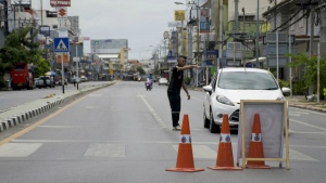 Authorities direct traffic after explosions occurred overnight and Friday morning in the tourist city of Hua Hin, Thailand on Friday, Aug. 12, 2016. (AP / Penny Yi Wang)