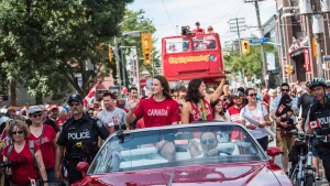 Team Canada's flag-bearer and gold medalist Penny Oleksiak, centre left, and fellow swim team member Michelle Williams ride in the back of a parade car for a Rio 2016 parade celebration in Toronto on Sunday August 28, 2016. (Aaron Vincent Elkaim / THE CANADIAN PRESS)