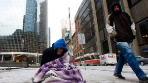 A homeless person panhandles for money during an extreme cold weather alert for the City of Toronto on Monday, December 13, 2010. (THE CANADIAN PRESS/Nathan Denette)