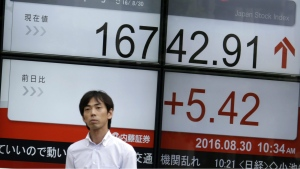 A man walks past an electronic stock board showing Japan's Nikkei 225 index at a securities firm in Tokyo, Tuesday, Aug. 30, 2016. (AP / Eugene Hoshiko)