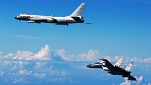 In this Sunday, Sept. 25, 2016, photo released by Xinhua News Agency, Chinese People's Liberation Army Air Force Su-30 fighter, right, flies along with a H-6K bomber as they take part in a drill near the East China Sea. (Shao Jing/Xinhua via AP)