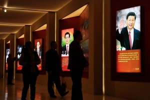 Visitors walk past images of China's past and present leaders, from left, Mao Zedong, Deng Xiaoping, Jiang Zemin, Hu Jintao and Xi Jinping on display at an exhibition on the Long March at the military museum in Beijing, Monday, Oct. 24, 2016. (AP Photo/Andy Wong)