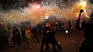 Revellers dressed as demons called 'Dimonis' hold fireworks as they take part in a 'Correfoc' or 'run with fire' party during traditional celebrations in honor of Saint Anthony in Muro village in the Mediterranean island of Mallorca, Spain, on  Monday, Jan. 16, 2017. Mixing pagan and religious traditions from medieval times, the fire and demon festivals are held in towns across the island of Mallorca each Jan. 16-17 to celebrate the day of Saint Anthony the Abbot, the patron saint of animals. (AP Photo/Francisco Seco)