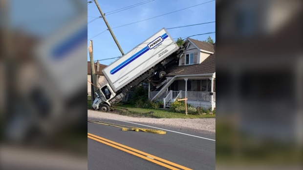 Commercial truck wedged in between pole and house